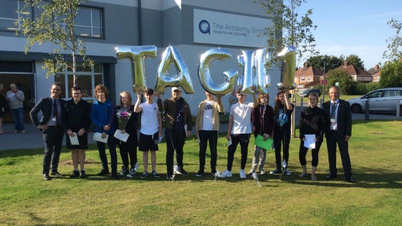 TAG learners holding TAG#1 balloons